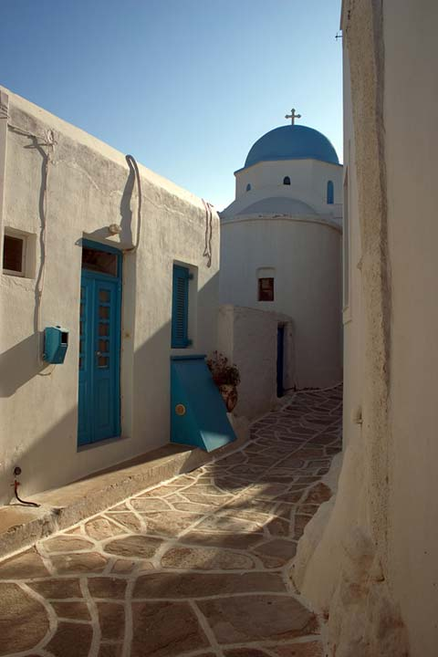 WHITE AND BLUE - A peaceful stroll among the medieval streets of a Greek Island village can lead to chapels like this. I love the afternoon sun, the soft playful light and the shades the buildings create. The chapel can be found on Paros island in a vilage called Lefkes. by Nikos Bournas